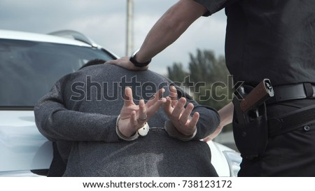 Police officer arresting criminal, putting him on car trunk and reading rights for him.