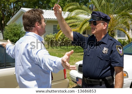 Police officer giving a field sobriety test to a drunk driver.