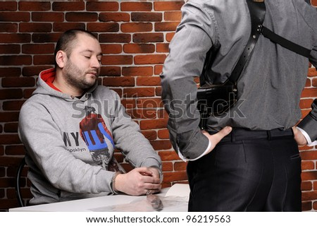 Police officer interrogates detainee against a break wall - stock photo