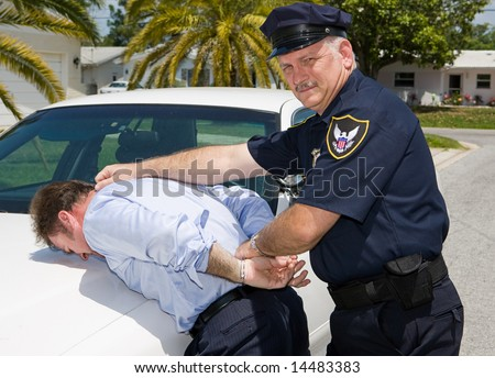 Police officer looking at camera as he arrests a suspect.