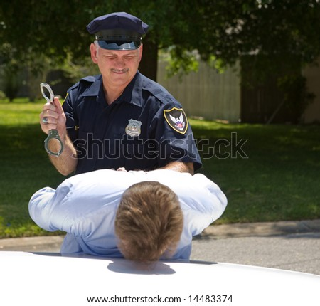 Police officer preparing to handcuff a suspect.