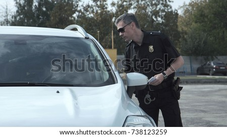 Police officer stopping the driver of a vehicle and questioning him over an alleged offence through the open window of the car