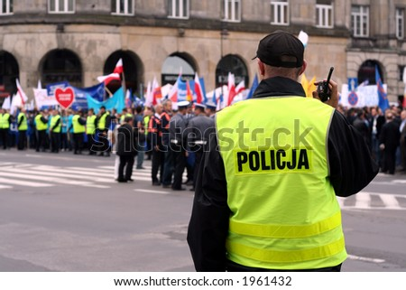 Police officer talking on a radio during an anti-government demonstration in Warsaw Poland on 7 Oct 2006 (Blue March by Platforma Obywatelska). Purposely taken with a shallow DOF not to detail faces.