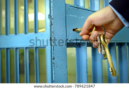 Police officers locks the door in prison corridor.