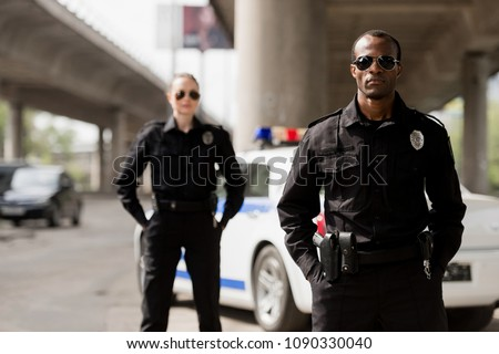 police officers with hands in pockets looking at camera in front of car