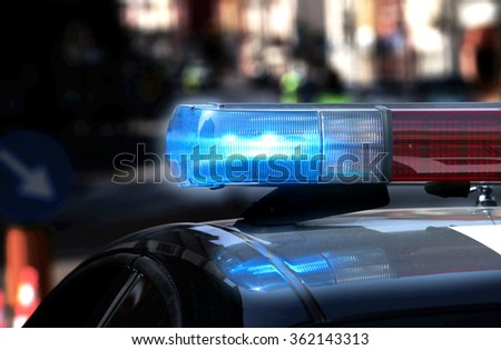 Police patrol car with flashing lights and siren on during the night raid against crime
