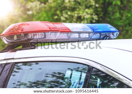 Police patrol car with sirens off during a traffic control. Blue and red flashing sirens of police car during the roadblock in the city.