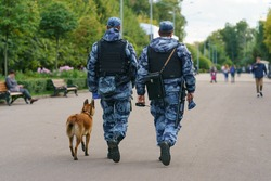 Police patrol in the public city park of Moscow. Two officers with dog. Safety and security concepts. Backs, rear view. Coronavirus pandemic time.
