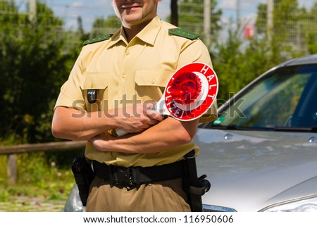 Police - policeman or cop in uniform stop car in traffic control