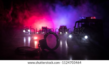 Police raid at night and you are under arrest concept. Silhouette of handcuffs with police car on backside. Image with the flashing red and blue police lights at foggy background. Slider shot
