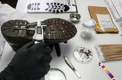 Police scientist investigates with a scale on a shoe sole tape tread involved in crime lab murder, concept image