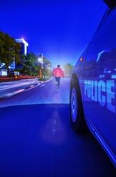 Police Sedan car speeding in the night through traffic lights, chasing a thief motion blur, Gaborone, Botswana,