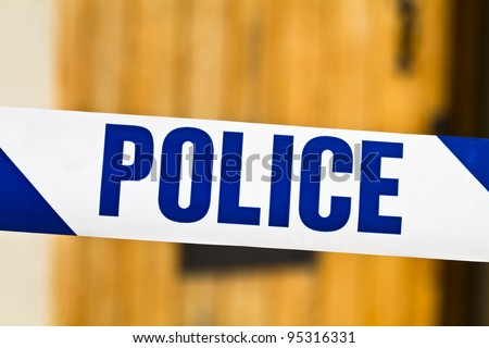 Police tape across an open door - stock photo