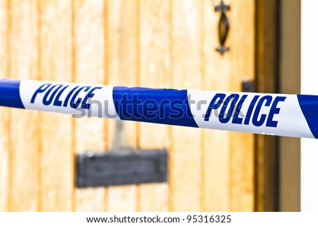 Police tape strung across a front door with shallow depth of field
