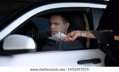 Police woman giving fine receipt to driver on road, traffic offence, inspection Foto stock ©