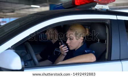 Police woman receiving call on car radio about accident, patrolling with mate Foto stock ©