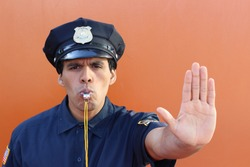 Policeman blowing whistle and showing stop hand gesture