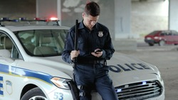 Policeman cops stand near patrol car use phone accepting emergence call enforcement talk officer police uniform auto safety security communication control policeman slow motion