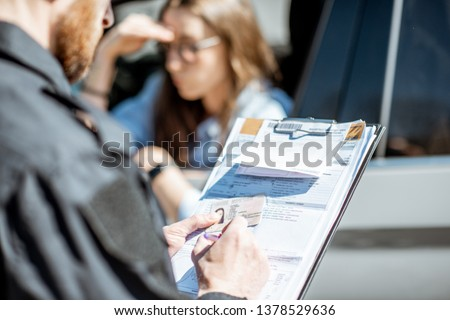 Policeman issuing a fine for violating the traffic rules to a young woman driver, close-up view focused on the folder