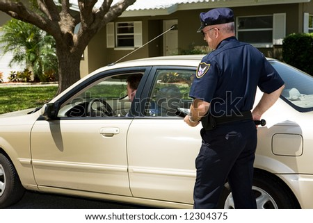 Policeman pulling over a motorist on the street.