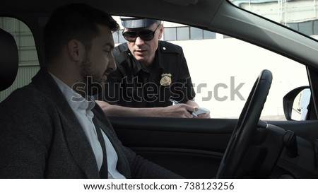 Policeman stopping a driver in a car to question him through the window on a traffic offence