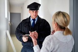 Policeman talks to wife at witness interview at the front door after a burglary
