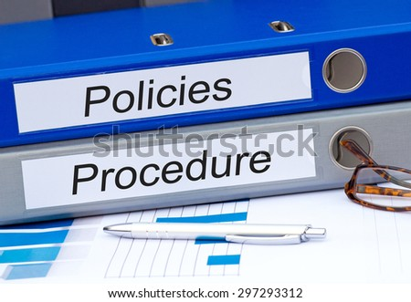 Policies and Procedure - two binders on desk in the office #297293312