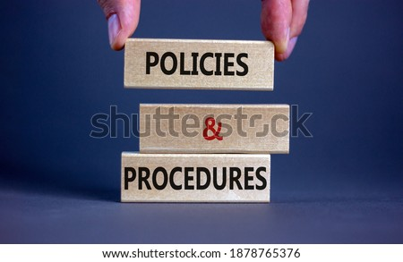 Policies and procedures symbol. Wooden blocks form the words 'Policies and procedures' on grey background. Male hand. Business and policies and procedures concept. Copy space. Сток-фото ©