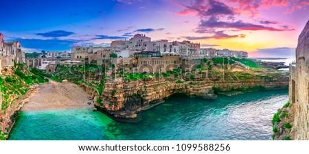 Polignano a Mare, Puglia, Italy: Sunset at Cala Paura gulf with Bastione di Santo Stefano and Lama Monachile beach in background, Apulia, Italy, province of Bari #1099588256