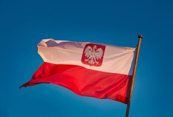 Polish flag against the sky. Concept of Polishness, independence day. The flag of Poland with the Polish emblem flutters in the sky.