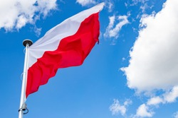 Polish flag on a background of the cloudy sky. National symbol of Poland on the mast. Summer season.