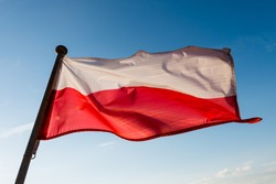 Polish flag on the mast against blue sky