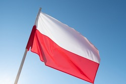 Polish flag waving in wind and sunlight. Flag of Poland on blue sky background.
