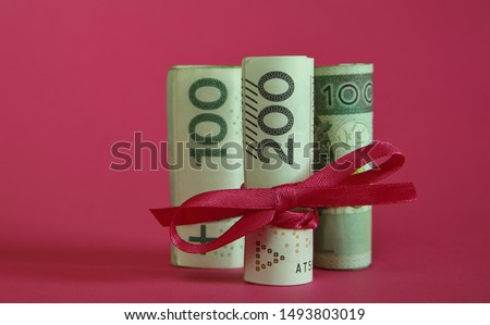 Polish money banknotes 200 rolled and tied with red ribbon, behind two rolls of 100 Polish zloty in soft focus, isolated on pink background, close up, concept of financial gift, present