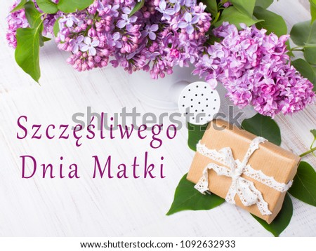 Polish Mother's day card, with words: Happy Mother's Day. Lilac flowers, gift box on white wooden background Zdjęcia stock ©