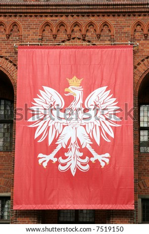 Polish national flag hanging on an old Gothic wall