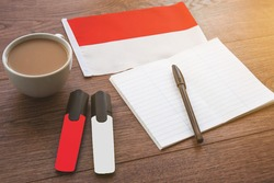 polish national flag, pen, notebook, markers and a cup of coffee on a wooden table, foreign language learning concept
