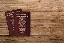 Polish passports on a wooden background, Polish nationality