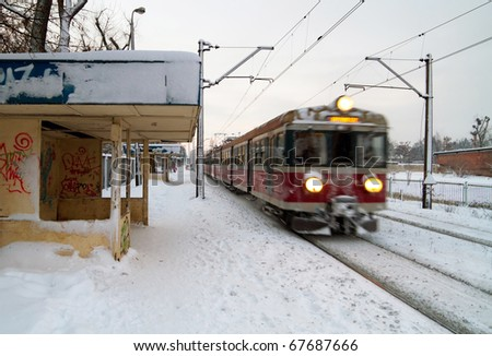 Polish train station at winter with train in motion