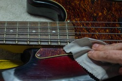polishing electric bass guitar with microfiber cloth
