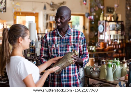 Polite craftsman offering earthenware to young woman in shop of pottery