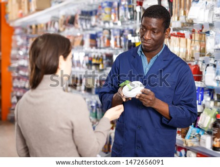 Polite salesman offering materials and tools to young woman in shop of household goods