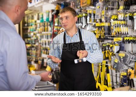Polite salesman offering tools to man in hardware shop