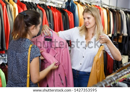 Polite smiling glad  cheerful positive seller communicating with female customer in leather clothes shop