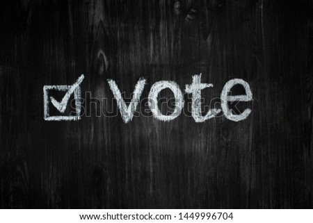 "Political activism sign: handwritten word ""vote"" in black background. Election process concept: word vote and an filled-in tick box in wood low-key background"