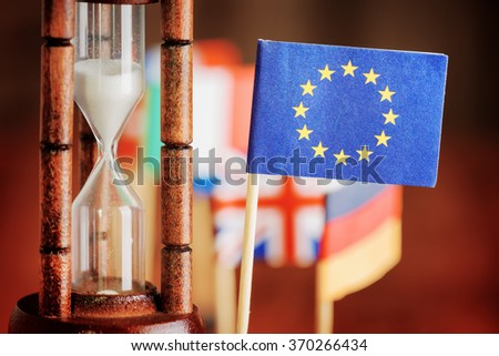 Political concept with flag of the European Union. Time is running out. Closeup view of hourglass and flag of the European Union. Flags of European countries in background. #370266434