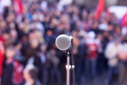 Political protest. Demonstration. Microphone in focus against blurred crowd.