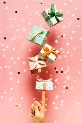 Polka dot pattern gift box with ribbon falling and female hands on pink background, levitation, creative pastel, vertical