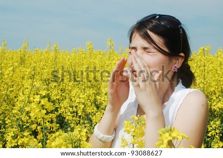 Pollen allergy, girl sneezing in a field of flowers