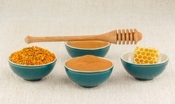 Pollen granules, honeycomb, honey and cinnamon in green porcelain bowls with wooden dipper, on rustic table cloth